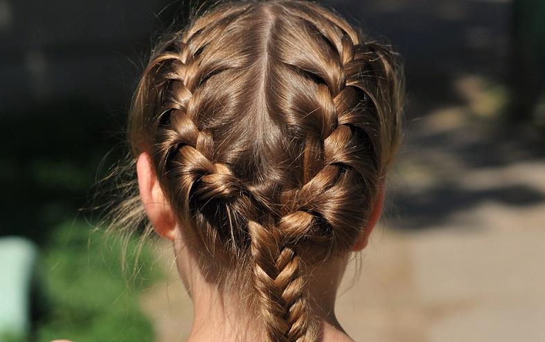 Die Haare werden dafür in der Mitte abgeteilt und an den Seiten sowie am Oberkopf in je eine Strähne geteilt.  ( Foto: Shutterstock-Nataliya Kuznetsova )